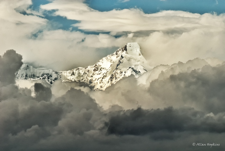 A peak from the Himalayan Nanda Devi Range emerging above rain clouds - © flickr user
