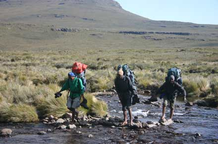 Our porters crossing a stretch of water - © William Mackesy